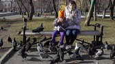 голубь : Mother and daughter eat buns and feed pigeons, sitting on a bench in a cold overcast afternoon. Young family at lunch outdoors. A brunette woman and a little girl are dressed in warm outerwear.