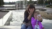 blogger : Mother and cute little daughter having fun and doing selfie in the park next to the fountain.
