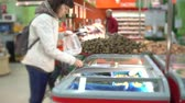 thirties : A young woman chooses a green frozen string bean in a self-service store. A girl is buying vegetables in a supermarket.