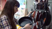 cast : A young woman chooses a convenient cast-iron frying pan in the section of the kitchen goods of the hypermarket.