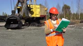 miner : A young woman worker in sunglasses stands near a mining excavator, looking over project.