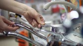 su tesisatı : A young woman chooses and buys a mixer tap in the supermarket in the department of household goods. Stok Video