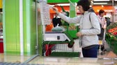 vinheta : A young woman weighs a green string beans on an electronic scales in a self-service store. A girl buys vegetables and fruits in a supermarket.