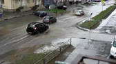 грязный : Flooded city road with big puddle of water spray from the wheels. Splash by car as it goes through flood water after heavy rains.