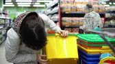 érckoporsó : A young woman and a little girl choose a large bright plastic container for toys in the supermarket. Mom shows the box to the daughter, who sits in a cart.