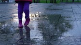 à prova d'água : A cute little girl in a red raincoat jumping over a puddle in the park at sunset. The child smiles and enjoys the fun, slow motion. Vídeos
