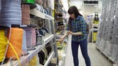 джут : A young woman in a blue checkered shirt chooses a solid multi-colored rope in a supermarket. Стоковые видеозаписи