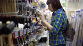 agd : A young woman in a blue checkered shirt picks a rubber mallet in the supermarket. Shes going to make repairs. Wideo