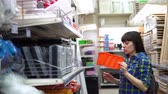 verificador : A young woman in a blue checkered shirt chooses a small container for self-tapping screws or tools in a building supermarket.