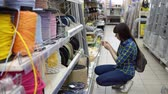 skein : A young woman in a blue checkered shirt chooses a solid multi-colored rope in a supermarket. Stock Footage