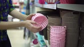 многоразовый : A young woman in a blue checkered shirt chooses and buys plastic baskets for things in the supermarket in the department of household goods. Стоковые видеозаписи