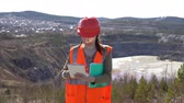 çukur : A young woman checks documents on a digital tablet, standing by an open-air career on a sunny day. She is wearing an orange vest and a protective helmet. Stok Video