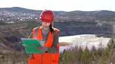 pit mine : A young woman checks documents against the background of an open-air career on a sunny day. She is wearing an orange vest and a protective helmet. Stock Footage
