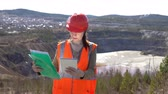 руда : A young woman checks documents on a digital tablet, standing by an open-air career on a sunny day. She is wearing an orange vest and a protective helmet. Стоковые видеозаписи