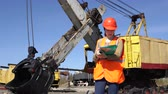 coal mine : A young worker in an orange waistcoat and a helmet stands near a mining excavator, looks through the document. Stock Footage
