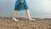 seguro : Female legs in protective blue shoes on the pebbly beach. The concept of safe recreation in the sea. Vídeos