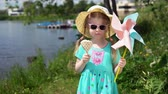pinwheel : A cute little girl is eating an ice cream in the shape of a heart, she stands on the seashore on a sunny summer day. The child holds a pinwheel in his hand. Stock Footage