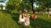 prohlížení : Mother and daughter in sunglasses have fun playing together on the grass under the young oaks at sunset. Young woman and little girl enjoy gadgets.