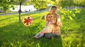 pinwheel : Mother and daughter in sunglasses have fun playing together on the grass under the oaks at sunset. A young woman and a little girl send an air kiss on the video link using the smartphone application. Stock Footage