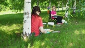 plasticina : A young mother and a pretty blonde daughter are engaged in creativity in a park in the shade under the trees. Having fun on a summer vacation, dolly shoot. Stock Footage