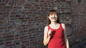 knír : Young happy woman holds a paper black mustache on a stick, standing next to a brick wall.