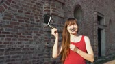 knír : Young happy woman holds a paper mustache and black retro hat on a stick, dancing next to a brick wall.