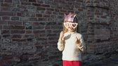 fingir : Little cute girl playing with paper phony glasses and a crown on a stick next to a brick wall.
