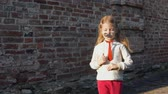 fingir : Little cute girl playing paper mustache and red tie on a stick next to a brick wall. Stock Footage