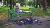 бросать : Little European girl feeding street pigeons with grain in the autumn park,slow motion.