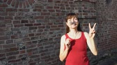 fingir : Young happy woman holds a paper black mustache on a stick and shows sign of victory, standing next to a brick wall. Stock Footage