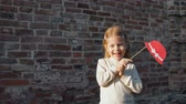 fingir : Little girl holding a paper red hat on a stick, standing next to a brick wal. Stock Footage
