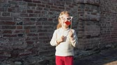 knír : Little cute girl playing paper sham glasses and red lips on a stick next to a brick wall.