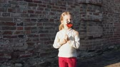 knír : Little cute girl playing paper mustache and red lips on a stick next to a brick wall.
