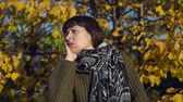 congelação : A young sick woman in a green knitted sweater strokes her head against the background of yellow foliage in the city park in Indian summer.