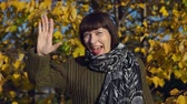 congelação : A young happy woman in a green knitted sweater waves her hand and greets someone against the yellow foliagein the city park in Indian summer. Stock Footage