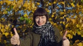 congelação : A young woman in a green knitted sweater shows thumbs up against the background of yellow foliage in a city park in Indian summer.