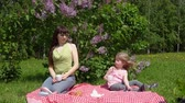 leylak : A dark-haired mother and a little blonde daughter play with a pinwheel and drink tea from white cups, they sit on a checkered blanket and enjoy a warm spring day next to a blooming lilac.