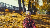setembro : Little cute girl in pink jumpsuit plays with yellow leaves in the city park in the Indian summer, slow motion.