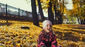 říjen : Little cute girl in pink jumpsuit plays with yellow leaves in the city park in the Indian summer, slow motion.