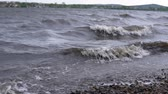 fırtınalı : Dark muddy waves with white foam on the pebble beach after the storm, slow motion.