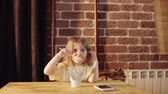 jogurt : A cute little girl eats yogurt from a big white jar near a brick wall for Breakfast. The child is dressed in yellow pajamas. Wideo