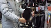 úsek : A young woman in a gray coat chooses a non-stick frying pan in the supermarket in the kitchenware department.
