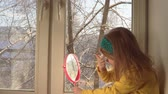 portrait shot : Little cute girl in a mustard jacket and a blue bandage puts makeup looking in a pink mirror, she sits on the windowsill, outside the window is a winter landscape. A child prepare for a carnival. Stock Footage