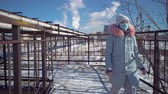 газ : A young woman in a protective mask and gray park goes over the bridge against the background of the pipes of a metallurgical plant on a winter day.