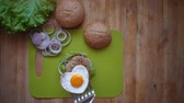 soğan : Flat lay of the process of cooking a burger overhead view the wooden table with ingredients and male hands.Male hands put a heart-shaped fried egg on a hot cutlet and bun