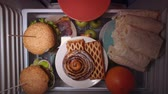 meia noite : Top view on the shelf of the refrigerator. Someone puts sweet pastries on a plate. Irregular nutrition and sleep disturbance.