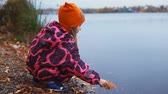 à prova d'água : Little blond girl in pink jumpsuit puts yellow autumn leaves on water. Child plays with fallen foliage in river, slow motion. Stock Footage
