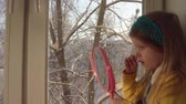 portrait shot : Little cute girl in a mustard cardigan and a blue bandage puts makeup looking in a pink mirror, she sits on the windowsill, outside the window is a winter landscape. A child learns to use cosmetics. Stock Footage