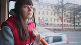 bonde : Young brunette woman in red sleeveless jacket stand in tram and looks out window while riding in public transportation.