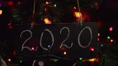 noel kartı : Close up of black letter board with number 2020 title on it hanging on branch Christmas tree among multicolor round bokeh in background, camera moves from right to left. Happy New Year greeting card.